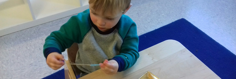 An IMA student in the Primary class does threading work
